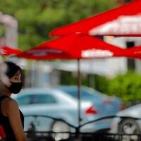 Une femme avec un masque sur la terrasse d'un restaurant