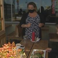 Jennie Silk sert deux clients assis à table à la terrasse du restaurant Uli's à White Rock