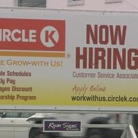 Une affiche du magasin Circle indique qu'elle embauche des employés, mais tout est écrit en anglais.