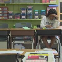 Une jeune fille assise à son bureau au retour en classe post-pandémie.