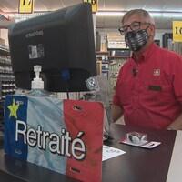Une personne âgé est à son poste, devant une caisse, dans une quincaillerie. Une pancarte au bas de l'écran indique 'retraité'.