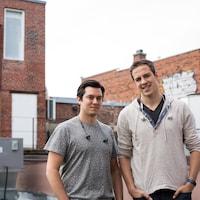 Deux jeunes hommes regardent vers la caméra sur le toit d'un édifice industriel.