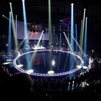 Scène circulaire plongée dans le noir, surplombée par des lumières et entourée de gens.
