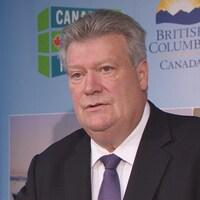 Le ministre de l'Énergie, des Mines et du Gaz naturel, Rich Coleman, en costume lors d'un point de presse