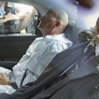 Richard Henry Bain assis dans un véhicule, tout habillé de blanc, les mains menottées.
