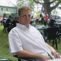 Photo de Richard Kachkar assis sur une chaise à l'extérieur.