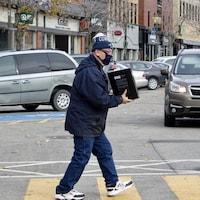 Un homme qui porte un masque traverse la rue devant des commerces et des voitures au centre-ville de Rimouski.