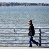Une personne marche sur la Promenade de la mer, à Rimouski.