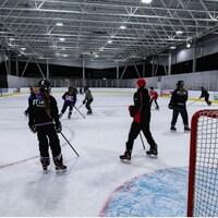 Des joueurs de ringuette sur une patinoire extérieure.