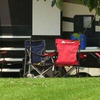 Des chaises de campings devant une roulotte.