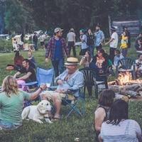 Des campeurs lors du festival River and Sky, assis dans l'herbe, avec des chaises et des feux de camp.
