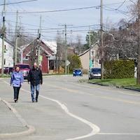 Deux personnes marchent sur un trottoir de Saint-Pascal.