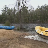 Sur la rive d'une rivière haute, deux embarcations pneumatiques, une bleue et une jeune, sont déposées.