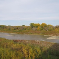 Des îlots de roches sont visibles dans la rivière Rouge, qui est entourée de végétation.