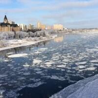 Vue de la rivière Saskatchewan Sud par une journée ensoleillée, des blocs de glace flottent sur l'eau.