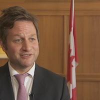 Le ministre de l'Éducation en entrevue à la caméra. Un drapeau du Canada figure derrière lui.