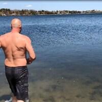 Un homme se dirige d'un pas assuré vers le lac. Il a de l'eau jusqu'aux genoux.