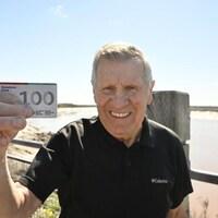 Robert Duguay pose fièrement avec sa carte de 100 dons de sang.