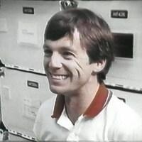 Robert Thirsk tout sourire, assis dans un simulateur de navette.