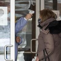 Une employée prend la température d'une femme à son arrivée au foyer de soins de longue durée Roberta Place.