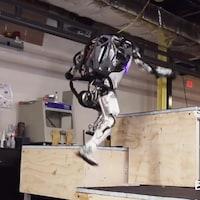 Une capture d'écran d'une vidéo montrant le robot humanoïde Atlas en train de sauter de côté entre deux marches d'une hauteur de quelques dizaines de centimètres.