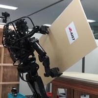 Une capture d'écran d'une vidéo montrant le robot HRP-5P en train de saisir une plaque de plâtre sur une table.