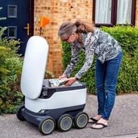 Une photo montrant une femme en train de prendre une colis dans un robot en forme de glacière sur roues.