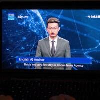 Un homme robot, vêtu d'une veste grise et portant des lunettes, lit les nouvelles en anglais.