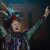 L'acteur Taron Egerton, qui incarne Elton John, a les bras levés en l'air et porte un costume multicolore couvert de fausses plumes.