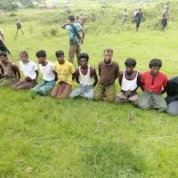 Dix hommes à genoux dans un champ avec les mains derrière le dos, entourés d'hommes armés.