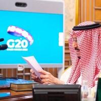 Salmane ben Abdelaziz Al Saoud regarde un document. Un écran derrière lui affiche le logo du G20.