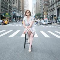 Une femme assise sur un banc au milieu d'une rue de New York.