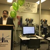 Le directeur se tient dans un atelier de couture où sont disposés des ballons et une affiche de la Fondation Trillium de l'Ontario.