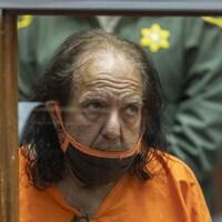 L'homme vêtu d'un habit de prison orange et portant un masque respiratoire se tient assis derrière une paroi vitrée, dans une salle d'audience.