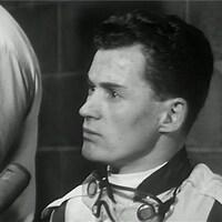 Ron Turcotte interviewé en combinaison de jockey, avec des lunettes au cou.