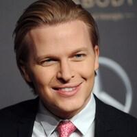 Un homme blond portant un complet et une cravate rose sourit aux photographes.