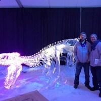 Ross et Antonio Baisas, médailles au cou, à côté de leur sculpture de glace d'un squelette de dinosaure.