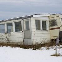 Une vieille roulotte de camping qui penche vers l'arrière.