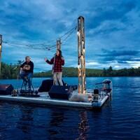 Une chanteuse et un guitariste font une prestation sur un quai flottant au milieu d'un lac, un peu avant le coucher du soleil.