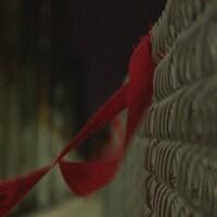 Un ruban rouge attaché à une clôture.