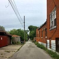 Une ruelle, des mauvaises herbes, un bâtiment en briques