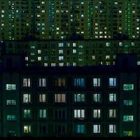 Les fenêtres de nombreux immeubles d'habitation sont éclairées dans la noirceur du soir.