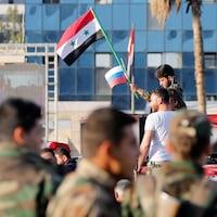 Un soldat syrien agite un drapeau russe ainsi qu'un drapeau syrien à Damas.