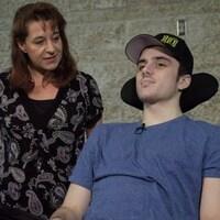 Un jeune homme est dans une chaise roulante. Sa mère se trouve à ses côtés.