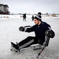 Ryan Straschnitzki jouant au hockey sur sa luge, derrière la maison familiale.