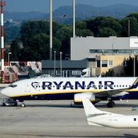 Un avion sur lequel on peut lire « Ryanair » est vu au sol près d'un autre avion. Un escalier permettant aux passagers de quitter l'avion est vu près de l'appareil.