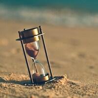 Un sablier dans le sable d'une plage.