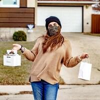 Dani Hackel, copropriétaire du magasin Mortise and Tenon, tient des contenants réutilisables en portant son masque.