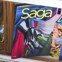 Une étagère avec des bandes dessinées, dont Saga au premier plan.