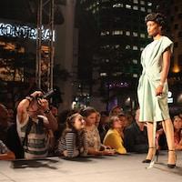 Le public observe la mannequin qui prend la pause sur la passerelle.